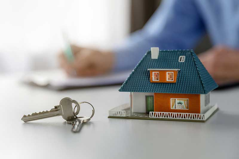 Miniature home with house key on closing day
